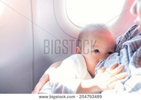 Asian mother is breastfeeding Cute little Asian 18 months toddler baby boy child on AirplaneToddler lying on mother's laps BreastFeeding in Public concept harsh sunlight overexposed at baby hand