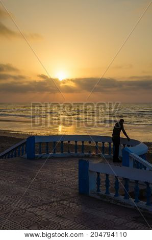 Silhouette of man standing at beach promenade with stone walkway during sunset at Sidi Ifni, Morocco, North Africa.