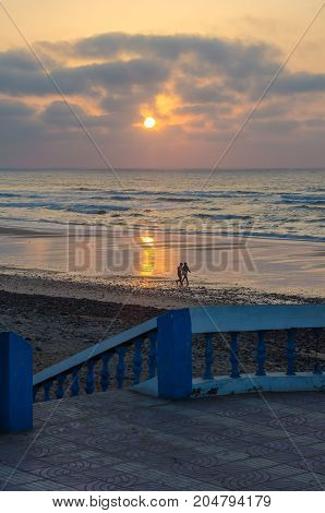 Two locals walking along beach promenade with stone walkway during sunset at Sidi Ifni, Morocco, North Africa.