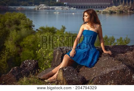 Beautiful young brunette woman, wearing blue dress, sitting on a cliff above the river with her eyes closed