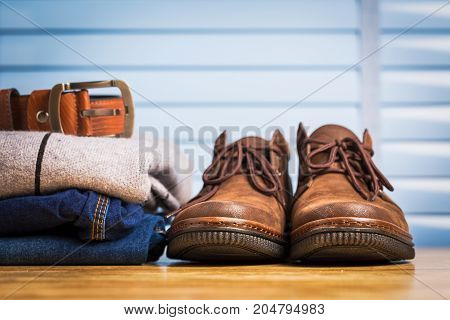 Men clothing asian style vintage with blue jeans pant and leather shoes in modern room with wooden table.