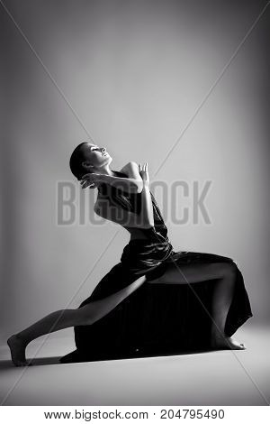 A beautiful athletic girl in a black dress is dancing.