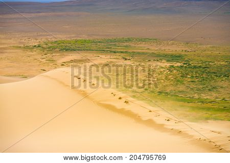 Wind blowing grains of sand from the top edge of the Khongor Els Sand Dune in the Gobi Desert in Mongolia