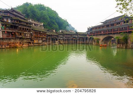 Riverside houses next to the Phoenix Hong or Huangsi Bridge in the center of traditional village of Fenghuang Hunan China