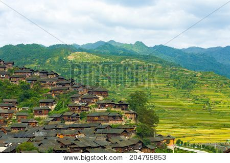 High angle view of mountains behind the traditional wooden houses of Xijiang Miao ethnic minority village in Guizhou China