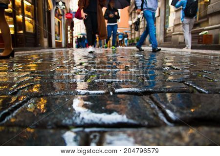 People walking on wet paving stones in rainy day in old town of Prague, Czech Republic