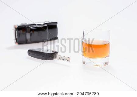 Do not drink and drive. Car keys next to a glass of brandy