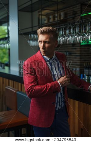 Young handsome model wearing striped shirt and classy red jacket posing confidently in bar.