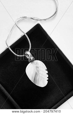 White nacre elegant pendant on silver chain in black jewel box