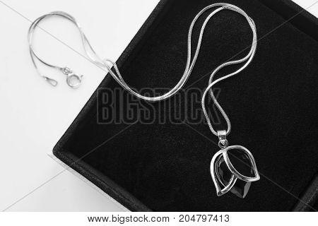 Black crystal pendant on silver chain in black jewel box