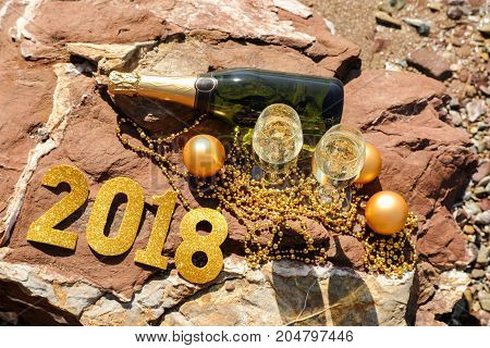 Champagne on a stony beach by the sea decorated in a New Year style numbers2018, New Year celebrate preparation concept. Horizontal. View from above.
