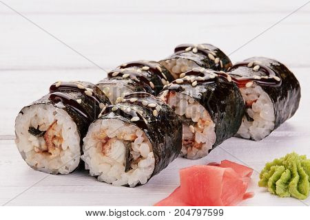Japanese Cuisine - Sushi and Rolls with Seafood Vegetables Cream Cheese on a white wood background. Rolls ginger wasabi chopsticks