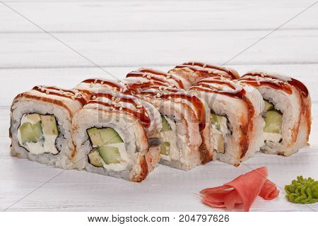 Rainbow Sushi Roll with salmon eel tuna avocado royal prawn cream cheese Philadelphia caviar chukka. Sushi menu. Japanese food. Chopsticks for rolls ginger wasabi over wooden white background
