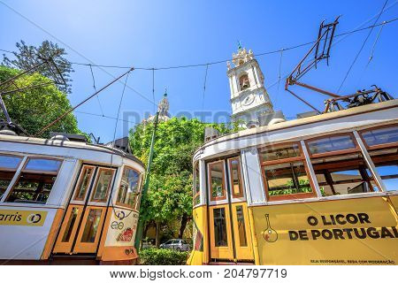 Lisbon, Portugal - August 27, 2017: two yellow historic Tram 28 in front of famous baroque and neoclassical Estrela basilica. Estrela is one of oldest districts of capital located on the western hills