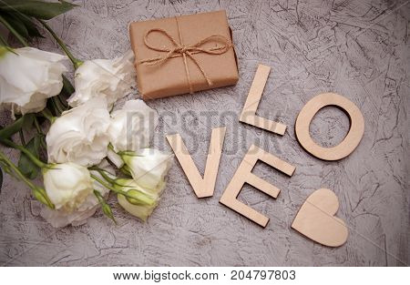 Love wooden letters inscription gift box and white flower bouquet on white wooden background