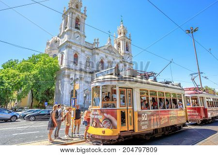 Lisbon, Portugal - August 27, 2017:tourists at terminus of historic Tram 28 in front of baroque and neoclassical Estrela Basilica.Estrela is one of oldest districts of capital located on western hills