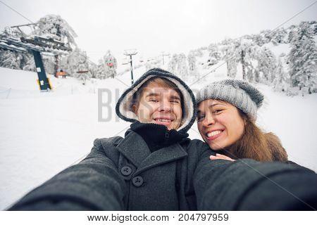 Happy boyfriend and girlfriend making selfie on a winter nature.