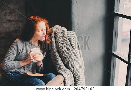 happy redhead woman relaxing at home in cozy winter or autumn weekend with book and cup of hot tea sitting in soft chair with blanket