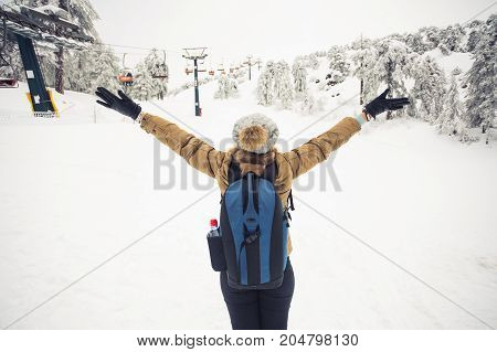 Happy girl standing back and hands up on winter nature background. Winter, vacation, weekend and freedom concept