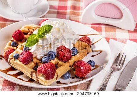 Belgian waffles with whipping cream and fresh berries
