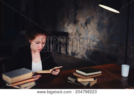 indoor portrait of beautiful redhead woman learning or reading books in university or library