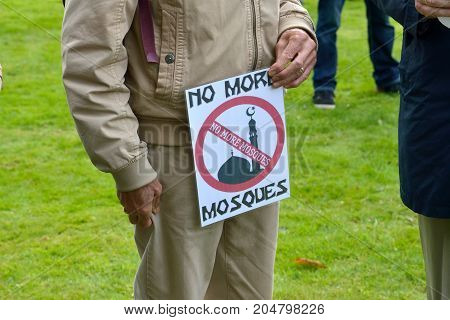 ENSCHEDE THE NETHERLANDS - SEPT 17 2017: An old man is holding a protest sign during an anti islam demonstration of Pegida. Pegida is a group of people who are against the islamization of Europe.