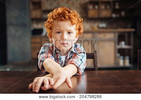 I am not in a playful mood today. Moody curly haired child sitting at a wooden table and stretching his hands while looking into the camera with eyes full of sadness.
