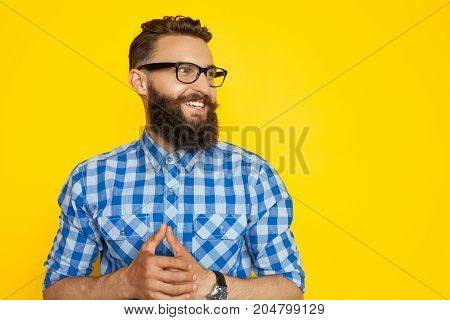 Young bearded man in checkered shirt and glasses posing happily looking away on orange background.