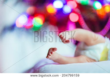 Closup of newborn baby feet and diaper with Christmas tree and colorful garland lights in the background laying on the ground showing cute little feet. Family, birth, celebration concept