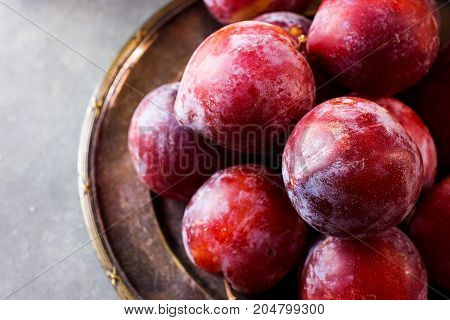 Ripe Juicy Colorful Red Organic Plums on Vintage Metal Plate. Dark Stone Background. Copy Space. Autumn Fall Harvest Thanksgiving.