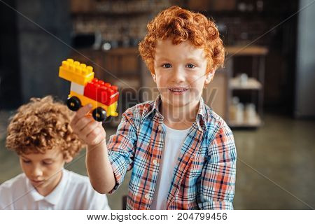 Look what I have. Waist up shot of a redhead curly boy looking into the camera with a cheerful smile on his face while sitting next to his older brother and playing with a construction set at home.