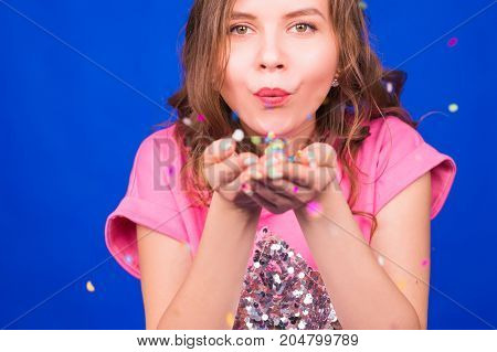 Close up portrait of attractive young woman blowing glitters. Caucasian Female model having fun over blue background