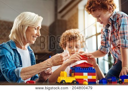 Grandchildren are a blessing from above. Selective focus on a beaming grandmother and a redhead little boy sitting on a dark wooden table building a dream house while spending time together and playing at home.