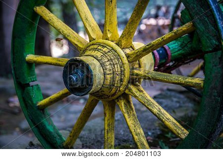 Old yellow wooden wheel of wagon close up outside