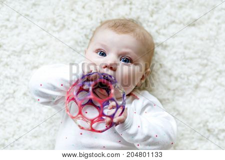 Cute adorable newborn baby playing with colorful ball toy on white background. New born child, little girl looking at camera. Family, new life, childhood, beginning concept. Baby learning grab rattle