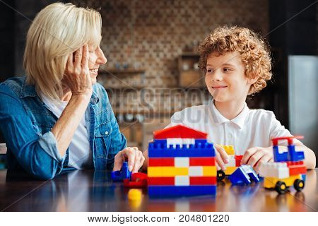 Love and understanding. Selective focus on a cute boy looking at his cheerful grandma with a slight smile on his face while both sitting at a table and playing with plastic building blocks at home.
