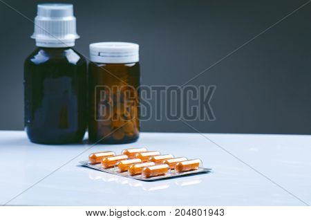 Pack of tablets isolated on a white background. Reflection of pills on a glass. Medicine´s background. Pharmacy. Close up of capsules. Medicines, supplements in a glass bottle.