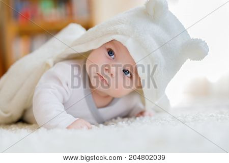 Baby girl with blue eyes wearing white towel or winter overal in white sunny bedroom. Newborn child relaxing in bed. Nursery for children. Textile and bedding for kids. New born kid with toy bear.