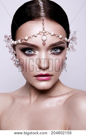 Portrait of a beautiful fashion brunette bride, sweet and sensual. Wedding make up and hair. Wight background. Art modern style. Blue eyes.