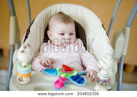 Cute adorable newborn baby sitting in swing. Closeup of peaceful child, little baby girl swinging and playing. Looking on toys. Family, birth, new life. Attentive child. Tiny girl and soft plush toy