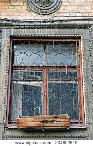 The old window with a lattice and a wooden box on the windowsill