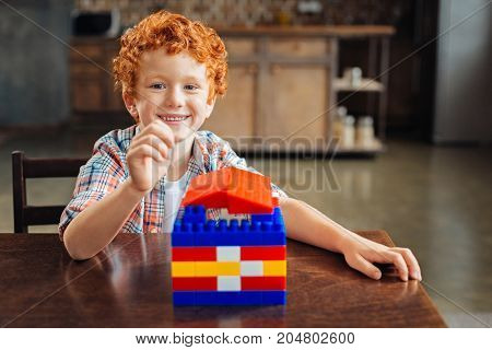 Look what I built. Adorable curly haired boy sitting at a table and getting excited after finishing his work on a colorful plastic house at home.