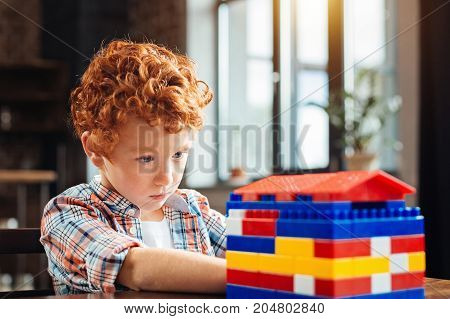 Attentive examination. Selective focus on a completely absorbed in the process of examination kid focusing his attention a colorful plastic house after playing with building blocks.