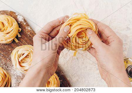 Woman Holding Raw Pasta Nest