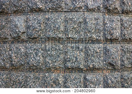 The gray wall of a large house made of stone bricks