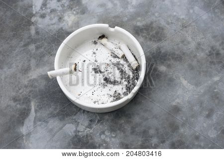 Cigarette stubs in the ashtray with table texture background.