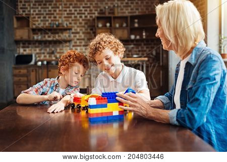 There is no place like home. Selective focus on smiling curly haired brothers playing with a building blocks and constructing cars while sitting at a table and chatting with their grandmother.