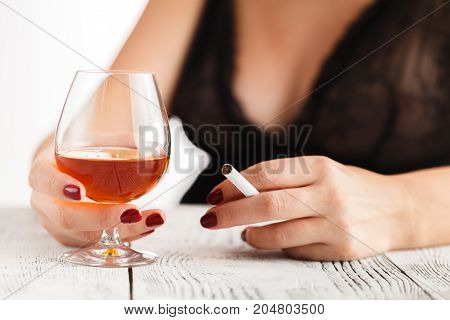 Woman In Lingerie Sitting At A Table And Drinking Alcohol