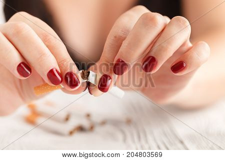 Woman Breaking Down Cigarette To Pieces. Quit Smoking Concept