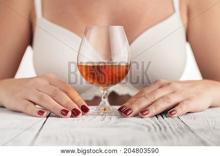 Beautiful young woman with cognac in hand